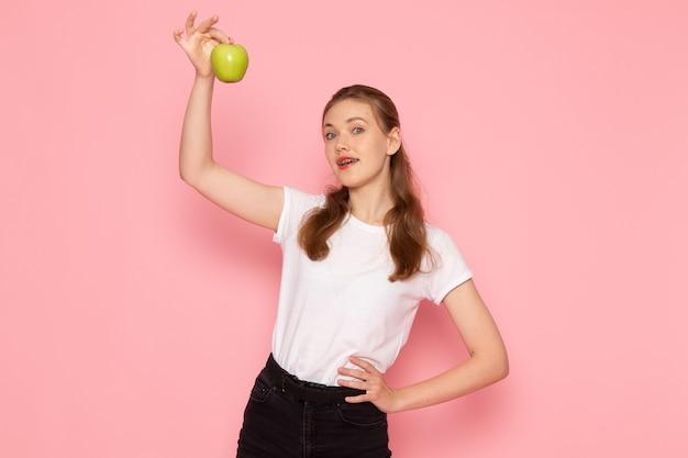 Vue de face de la jeune femme en t-shirt blanc tenant une pomme verte sur le mur rose