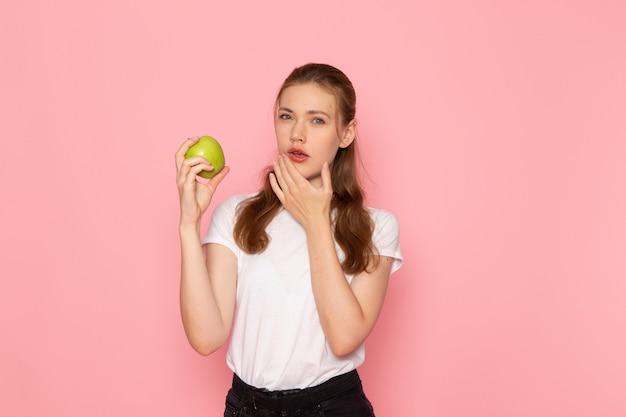 Vue de face de la jeune femme en t-shirt blanc tenant la pomme verte et la pensée sur le mur rose
