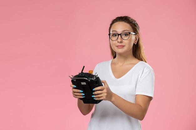 Vue de face jeune femme en t-shirt blanc tenant la télécommande sur le fond rose