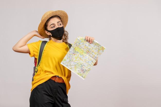 Vue de face jeune femme en t-shirt jaune brandissant la carte