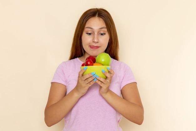 Vue de face jeune femme en t-shirt rose et blue-jeans tenant la plaque avec des fruits