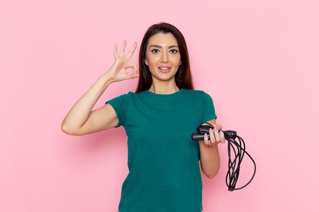 Vue de face jeune femme en t-shirt vert corde à sauter sur le mur rose clair taille sport exercices d'entraînement beauté mince athlète femelle