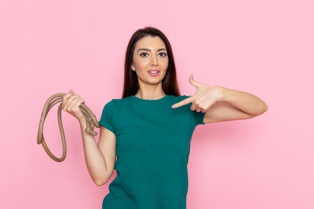 Vue de face jeune femme en t-shirt vert tenant la corde pour le sport sur le mur rose clair taille sport exercices d'entraînement beauté mince athlète femelle