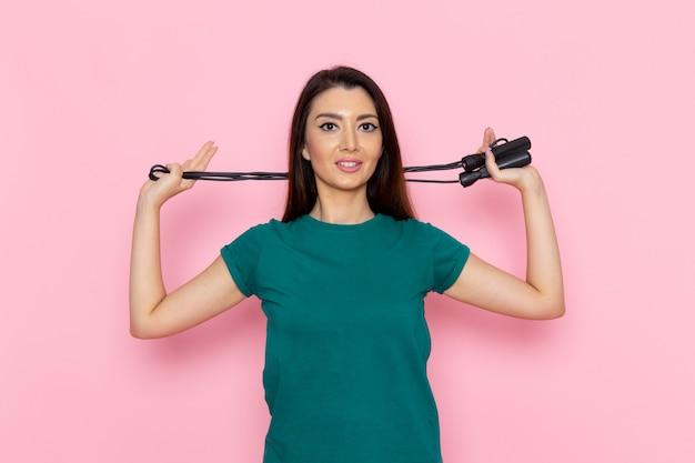 Vue de face jeune femme en t-shirt vert tenant la corde à sauter sur le mur rose clair taille sport exercice d'entraînement beauté athlète mince