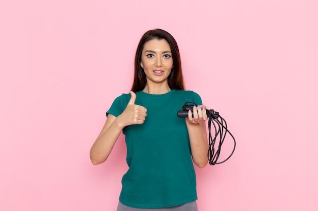 Vue de face jeune femme en t-shirt vert tenant la corde à sauter sur le mur rose clair taille sport exercices d'entraînement beauté athlète mince