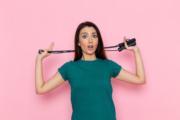 Vue de face jeune femme en t-shirt vert tenant la corde à sauter sur le mur rose taille sport exercices d'entraînement beauté athlète mince