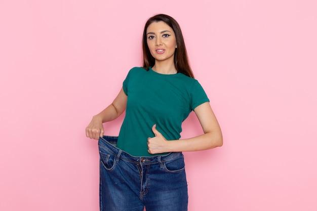 Vue de face jeune femme en t-shirt vert vérifiant sa taille sur le mur rose taille sport exercices d'entraînement beauté athlète mince