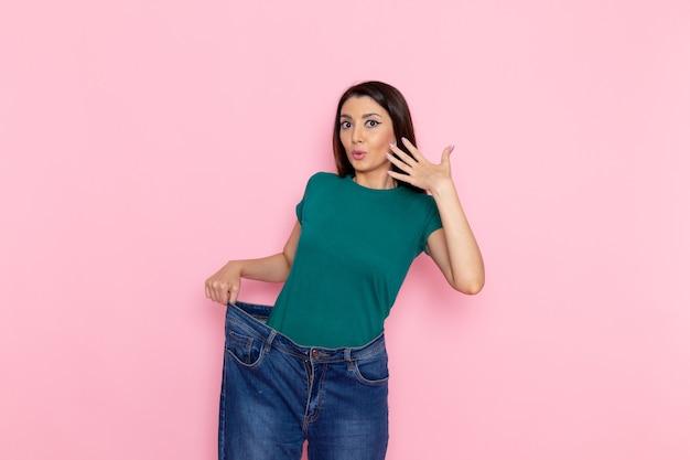 Vue de face jeune femme en t-shirt vert vérifiant sa taille sur le mur rose taille sport exercices d'entraînement beauté femme mince