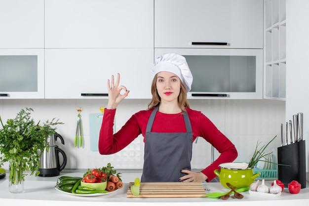 Vue de face jeune femme en tablier faisant signe okey