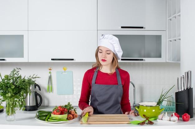 Vue de face jeune femme en tablier prenant un couteau