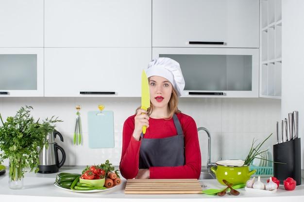 Vue de face jeune femme en tablier tenant un couteau