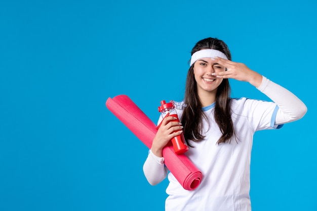 Vue de face jeune femme avec tapis pour les exercices et bouteille d'eau sur le mur bleu