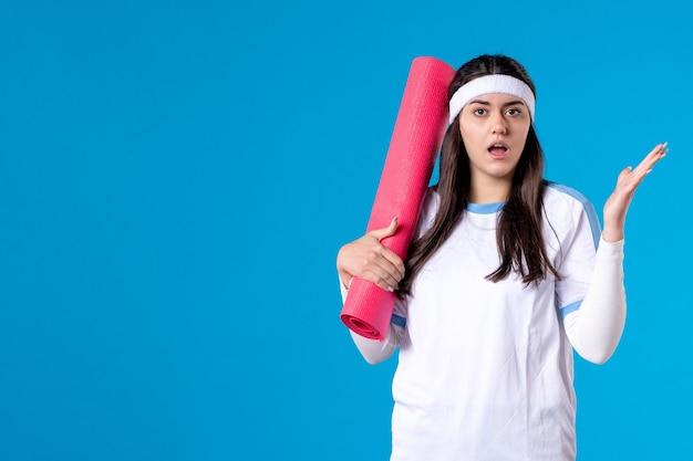 Vue de face jeune femme avec tapis pour exercices sur mur bleu