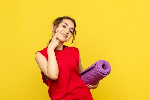 Vue de face de la jeune femme avec tapis violet sur mur jaune