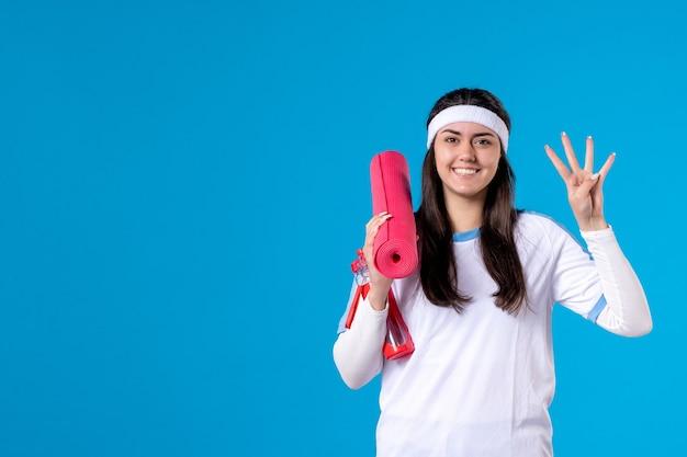 Vue de face jeune femme avec tapis de yoga sur mur bleu