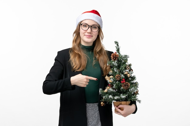 Vue de face jeune femme tenant arbre de vacances sur le sol blanc jouet de noël nouvel an
