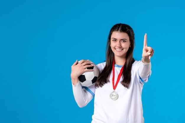 Vue de face jeune femme tenant un ballon de football sur un mur bleu