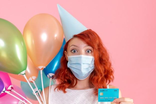 Vue de face jeune femme tenant des ballons colorés et carte bancaire sur rose