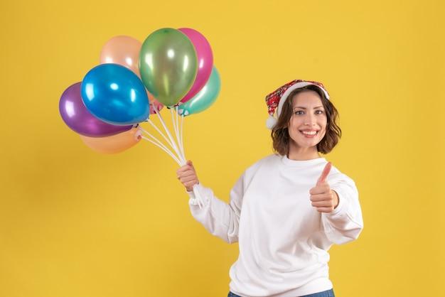 Vue de face jeune femme tenant des ballons colorés sur jaune