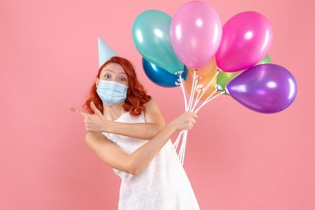 Vue de face jeune femme tenant des ballons colorés en masque sur rose clair