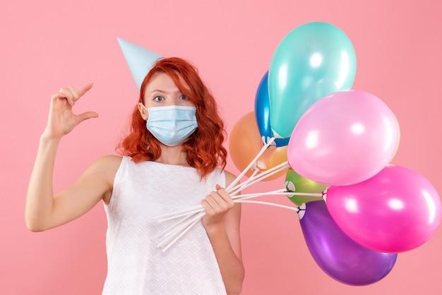 Vue de face jeune femme tenant des ballons colorés en masque sur le rose