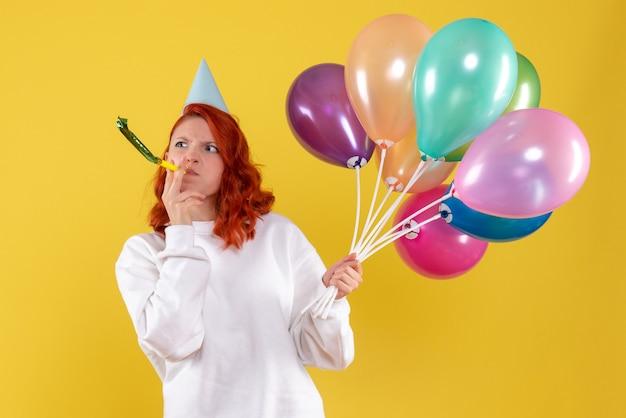 Vue de face de la jeune femme tenant des ballons colorés sur mur jaune