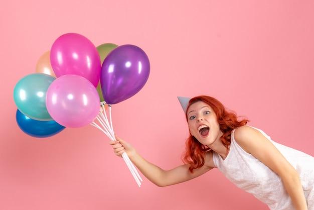 Vue de face de la jeune femme tenant des ballons colorés sur le mur rose