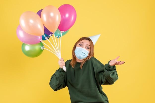 Vue de face jeune femme tenant des ballons colorés