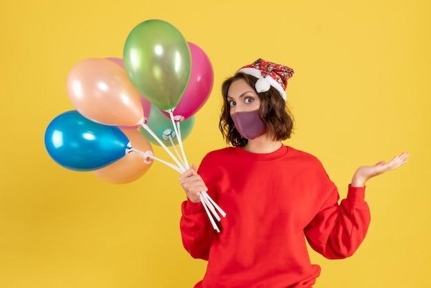 Vue de face jeune femme tenant des ballons en masque stérile sur bureau jaune nouvelle année couleur femme émotion fête célébration