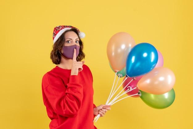 Vue de face jeune femme tenant des ballons en masque stérile sur jaune