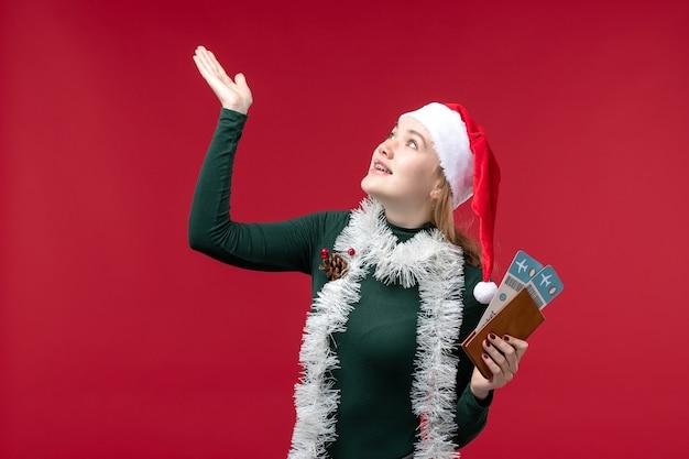 Vue de face jeune femme tenant des billets sur un bureau rouge