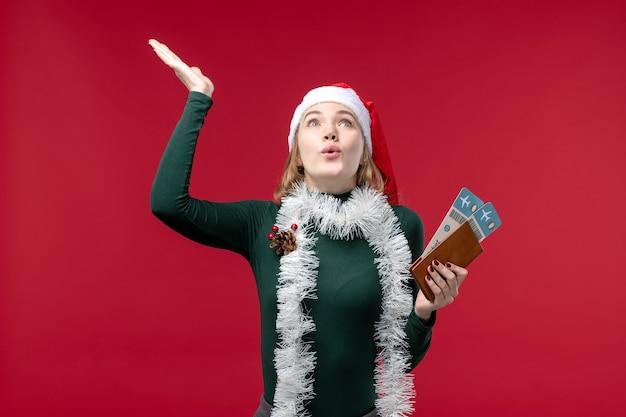 Vue de face jeune femme tenant des billets sur fond rouge