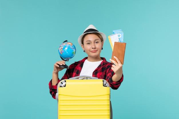 Vue de face jeune femme tenant des billets et un globe sur un bureau bleu