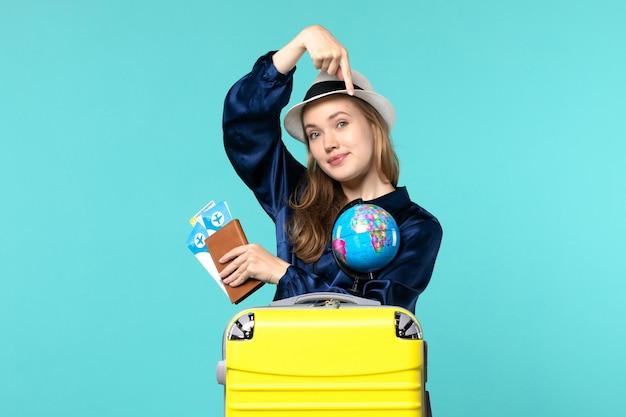 Vue de face jeune femme tenant des billets et globe sur le fond bleu avion voyage mer vacances voyage