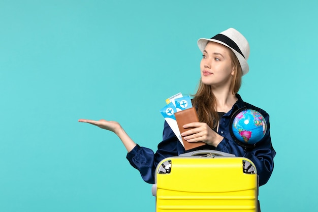 Vue de face jeune femme tenant des billets et globe sur fond bleu clair avion mer vacances voyage voyage