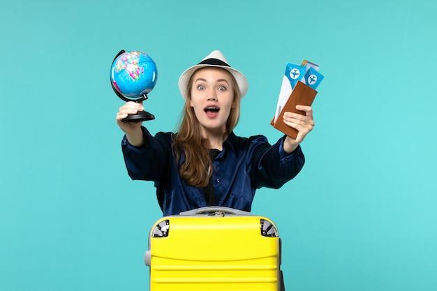 Vue de face jeune femme tenant des billets et petit globe sur bleu bureau avion vacances voyage voyage mer