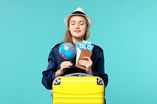 Vue de face jeune femme tenant des billets et petit globe sur fond bleu avion femme vacances voyage voyage mer