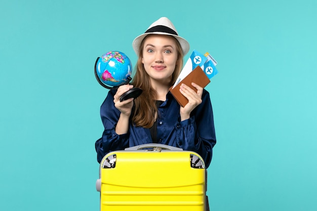 Vue de face jeune femme tenant des billets et petit globe sur le fond bleu avion mer vacances voyage voyage