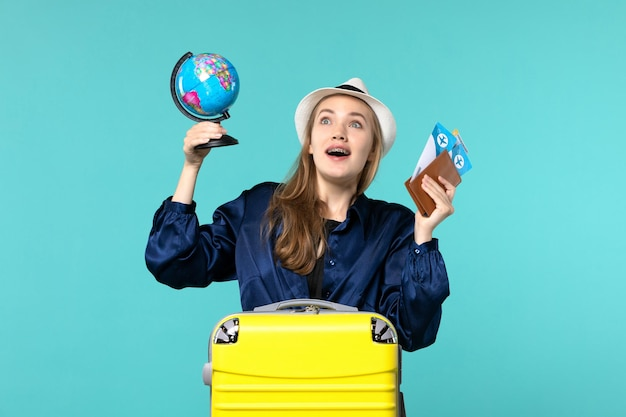 Vue de face jeune femme tenant des billets et petit globe sur fond bleu avion vacances voyage voyage mer