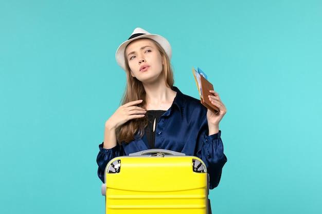 Vue de face jeune femme tenant des billets et la préparation pour les vacances sur le fond bleu avion voyage mer vacances voyage voyage