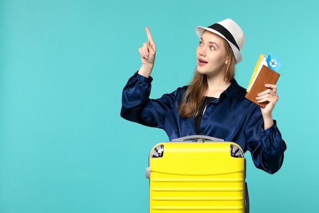 Vue De Face Jeune Femme Tenant Des Billets Et La Préparation Pour Les Vacances Sur Fond Bleu Voyage Mer Vacances Avion Voyage Voyage Photo gratuit