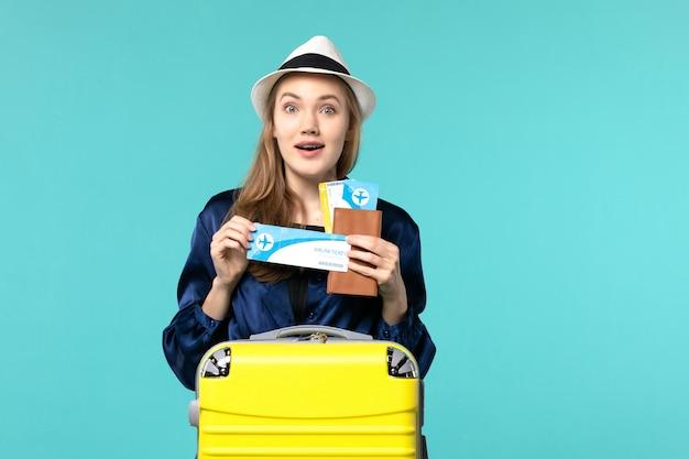 Vue de face jeune femme tenant des billets et la préparation pour le voyage sur le fond bleu voyage voyage avion mer vacances voyage