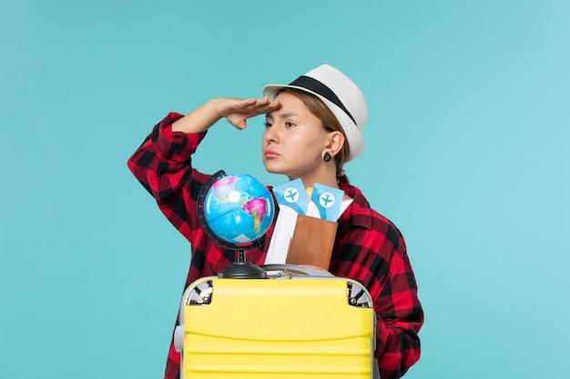 Vue de face jeune femme tenant des billets à la recherche à distance sur l'espace bleu