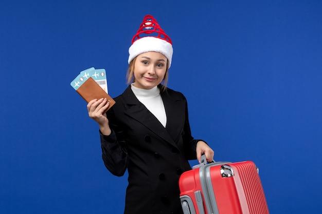 Vue de face jeune femme tenant des billets avec sac sur fond bleu vacances femme vacances