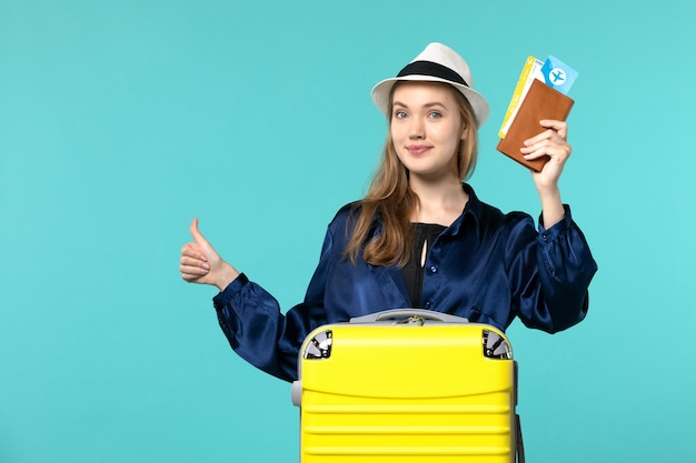 Vue de face jeune femme tenant des billets et se préparant pour les vacances souriant sur fond bleu voyage mer vacances voyage avion voyage