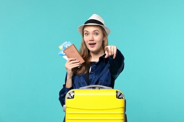 Vue de face jeune femme tenant des billets et se préparant pour le voyage sur le fond bleu voyage mer vacances voyage avion voyage