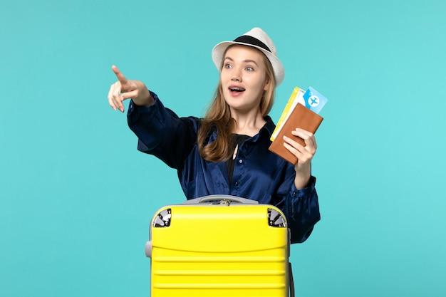 Vue de face jeune femme tenant des billets et se préparant pour le voyage sur fond bleu voyage mer vacances voyage voyage