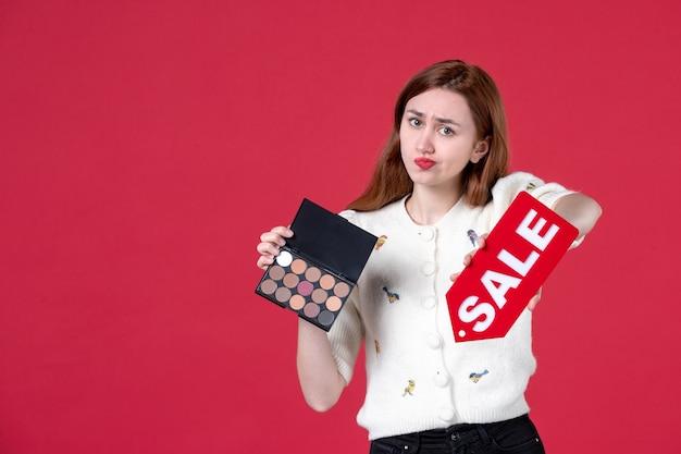 Vue de face jeune femme tenant une boîte à poudre et une plaque signalétique de vente rouge sur fond rouge femme shopping sensuelle couleur mars maquillage beauté mode lèvres