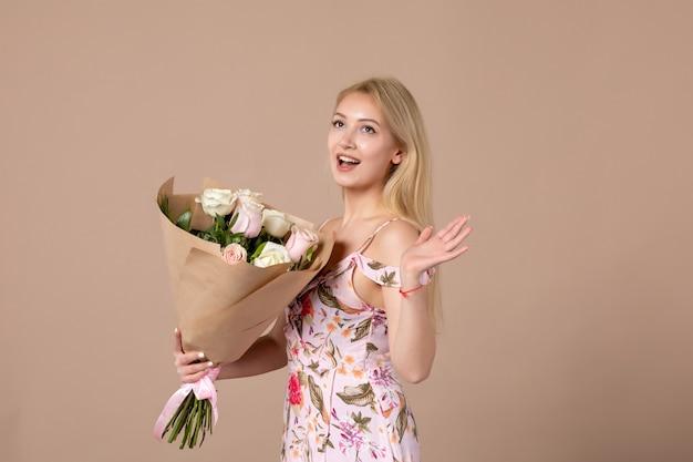 Vue de face d'une jeune femme tenant un bouquet de belles roses sur un mur marron