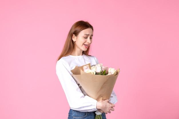 Vue de face jeune femme tenant un bouquet de belles roses sur rose